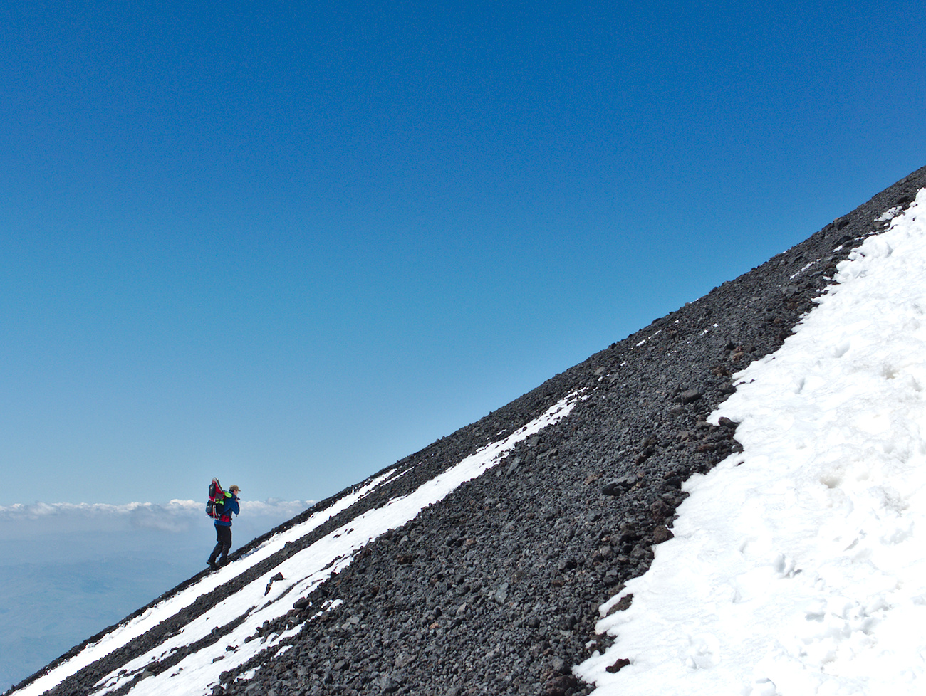 A tourist climbing one of the craters of the Etna vulcan, Sicily, Italy.
